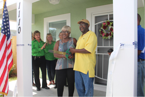 Linda-and-Henry-cuttin-ribbon-on-new-home